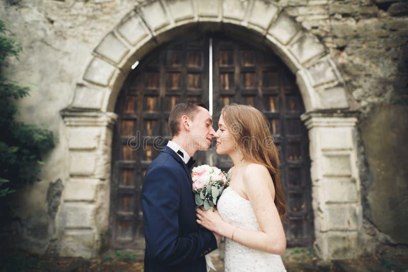 Schöne romantische Hochzeitspaare von den Jungvermählten, die nahe altem Schloss umarmen stockbild