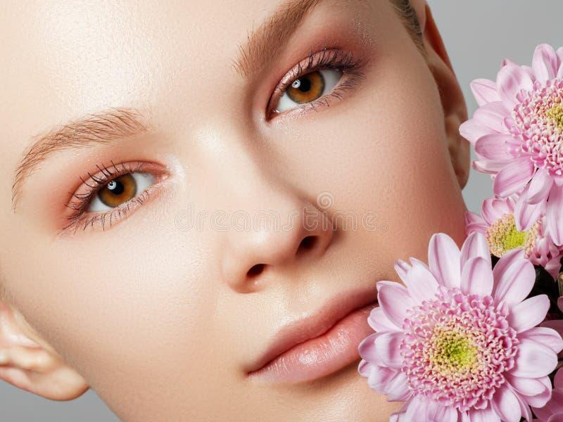Schöne romantische junge Frau in einem Kranz von den Blumen, die auf einem Hintergrund aufwerfen Inspiration des Fr?hlinges und d stockbilder