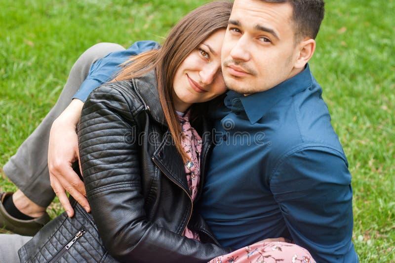 Schöne romantische Paare, die am Frühlingsgrünpark umfassen lizenzfreie stockbilder