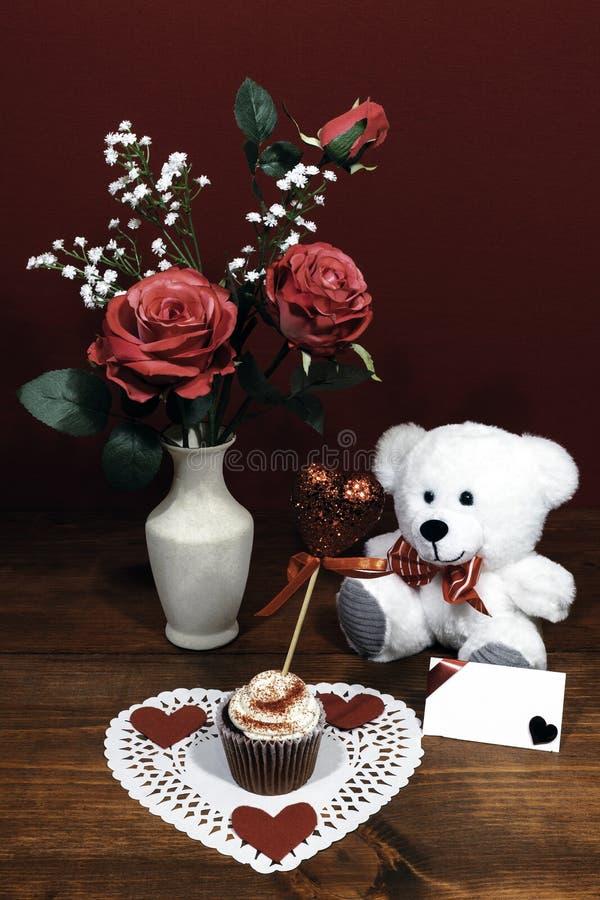 Schöne rosa Rosen in einem Vase, der mit Atemblumen des Babys betont wurde, Herz formten weißes dollie mit einem verzierten Schal stockfoto