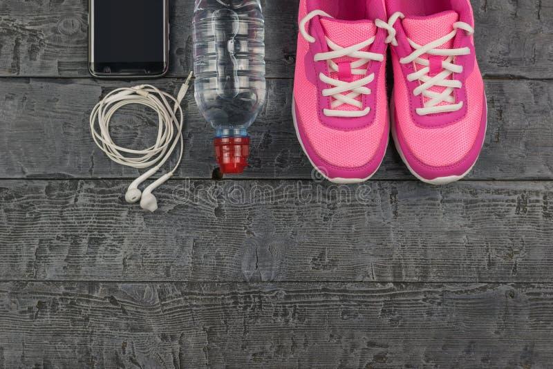 Schöne rosa Turnschuhe, Kopfhörer, Wasser und Äpfel auf einem hölzernen dunklen Boden Ansicht von oben lizenzfreie stockfotos