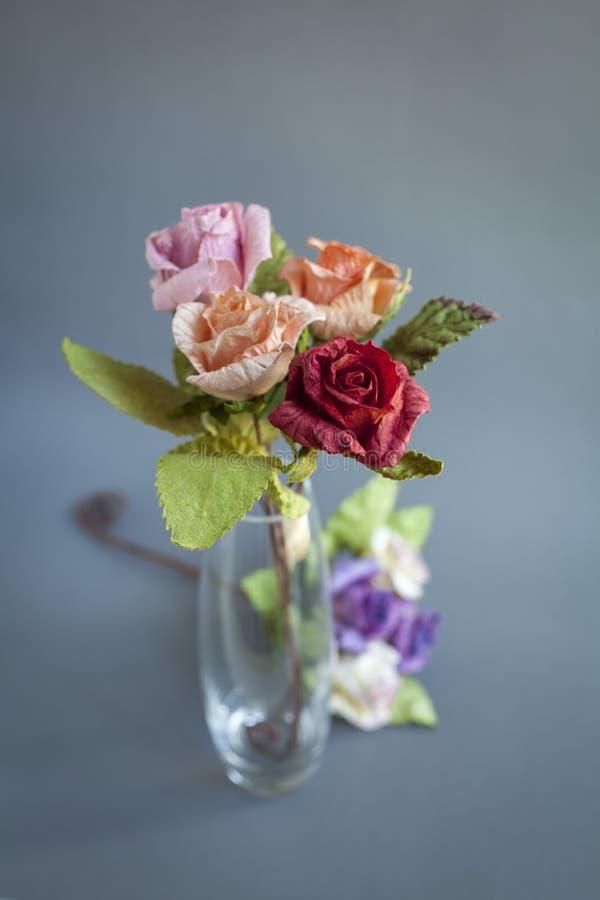 Schöne rosafarbene Papierblume im Klarglasvase über unscharfem grauem Hintergrund lizenzfreies stockfoto