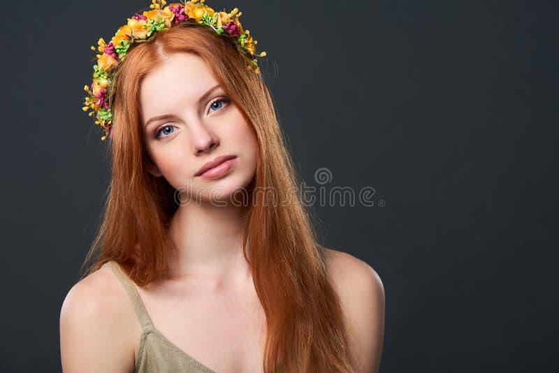 Schöne rote behaarte Frau im Blumenkranz lizenzfreie stockfotografie
