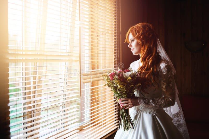 Schöne rote Haarbraut nahe Fenster lizenzfreies stockbild