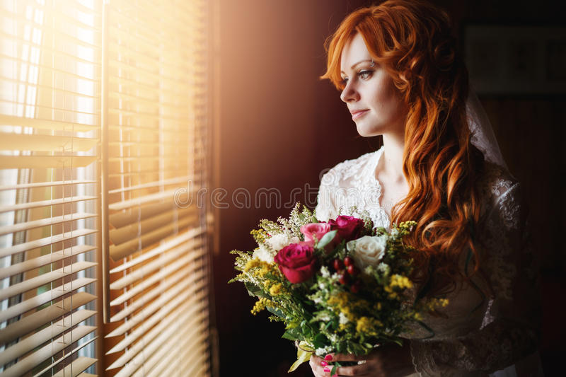 Schöne rote Haarbraut nahe Fenster stockfotografie