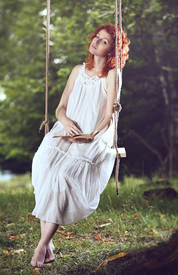 Schöne rote Haarfrau auf einem Schwingen lizenzfreies stockbild