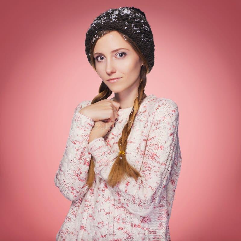 Schöne rote Haarfrau in der Winterausstattung: warme Strickjacke, Schal und Hut mit Schnee ganz über ihr Lokalisiert auf rosarote lizenzfreie stockfotografie