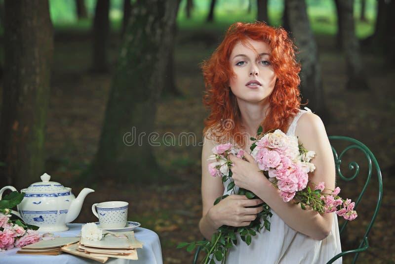 Schöne rote Haarfrau, die mit Blumen aufwirft lizenzfreie stockfotos