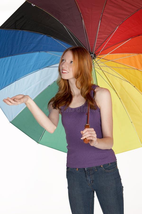 Schöne rote Hauptfrau mit Regenbogen-Regenschirm lizenzfreie stockbilder