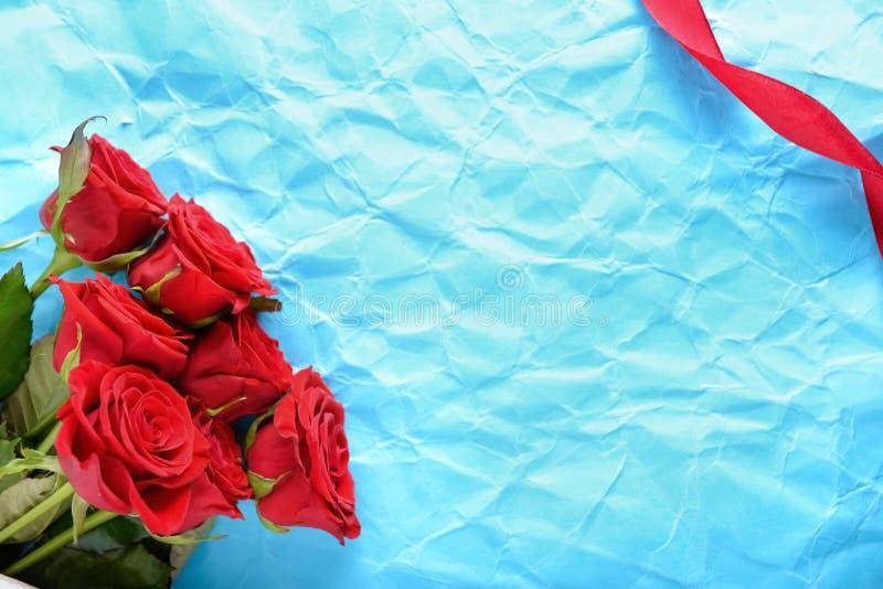 Schöne rote Rosen auf zerknittertem Packpapier lizenzfreie stockbilder