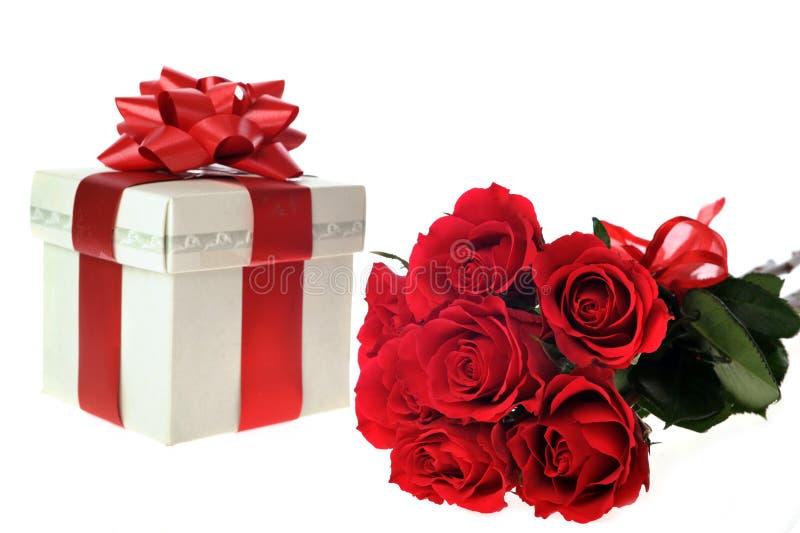 Schöne rote Rosen und Geschenk stockbilder