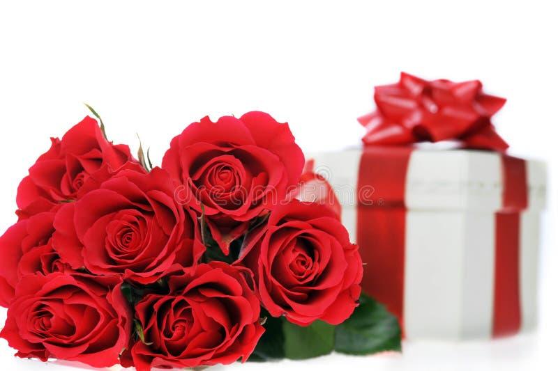 Schöne rote Rosen und Geschenk lizenzfreie stockfotos
