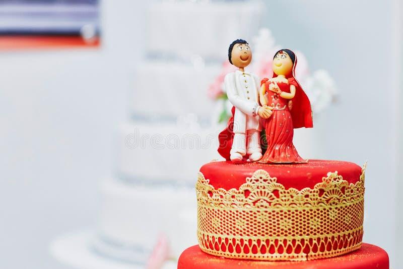 Schöne rote und gelbe Hochzeitstorte in der indischen Art lizenzfreie stockbilder