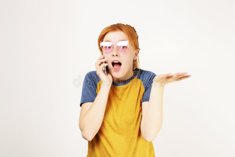 Schöne rote vorangegangene junge Frau, die lustige Gesichter mit Handy aufwirft, zeigt emotionale Gesichtsausdrücke und macht lizenzfreies stockfoto