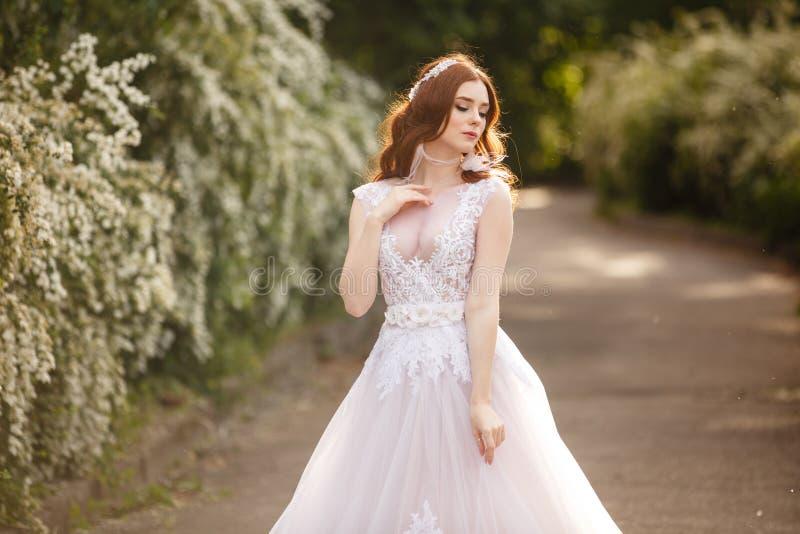 Schöne Rothaarige Braut im fantastischen Hochzeitskleid in blühendem Garten lizenzfreies stockbild