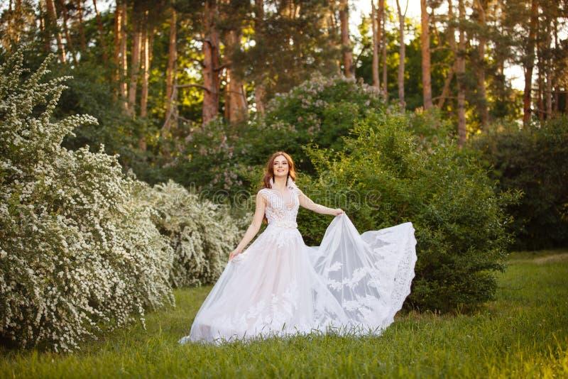 Schöne Rothaarige Braut im fantastischen Hochzeitskleid in blühendem Garten lizenzfreie stockfotos