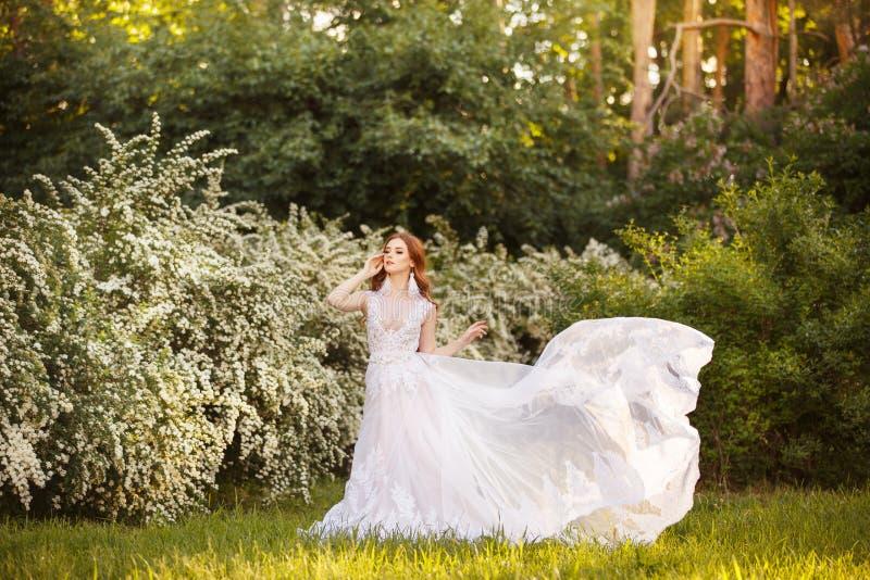 Schöne Rothaarige Braut im fantastischen Hochzeitskleid in blühendem Garten lizenzfreies stockfoto