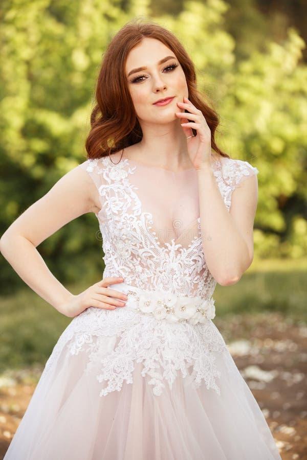 Schöne Rothaarige Braut im fantastischen Hochzeitskleid in blühendem Garten stockfotos