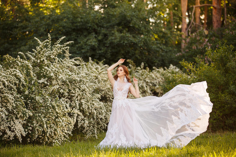 Schöne Rothaarige Braut im fantastischen Hochzeitskleid in blühendem Garten stockfotografie