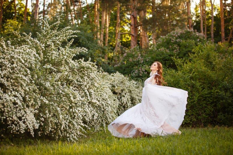 Schöne Rothaarige Braut im fantastischen Hochzeitskleid in blühendem Garten lizenzfreie stockfotografie