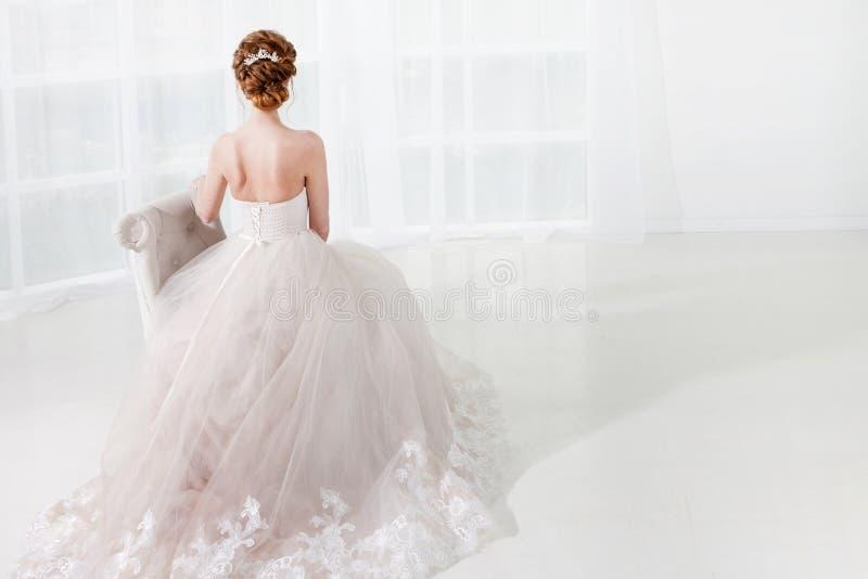 Schöne rothaarige Braut sitzt im Stuhl, stilvolle Frisur, hintere Ansicht Junge Frau im luxuriösen Hochzeitskleid lizenzfreie stockfotos