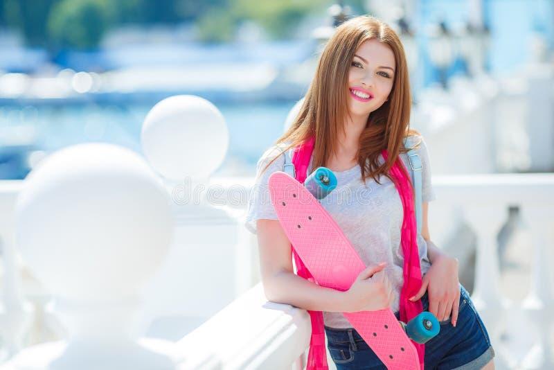 Schöne rothaarige Frau, die mit einem Skateboard aufwirft stockfotos