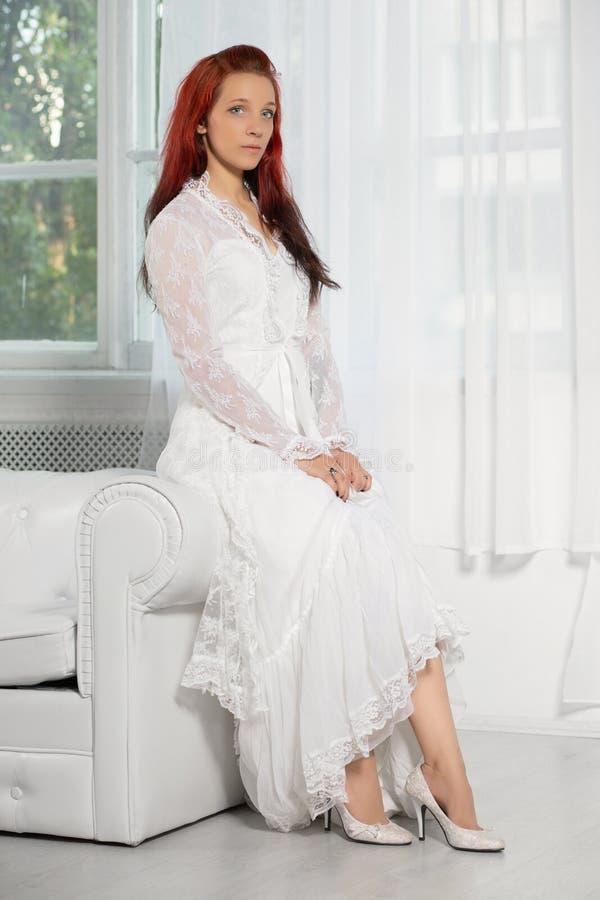 Schöne Rothaarigefrau, die im Studio aufwirft stockfoto