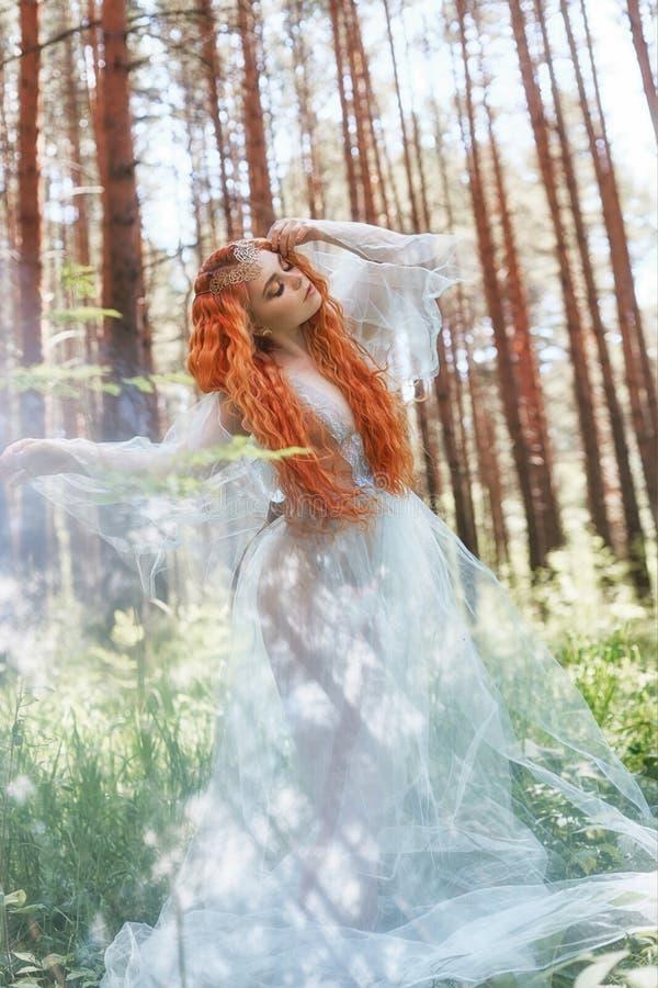 Schöne Rothaarigefrauen-Waldnymphe in einem blauen transparenten hellen Kleid im Wald, das in Tanz spinnt Rote Haarmädchen Kunstm lizenzfreie stockbilder