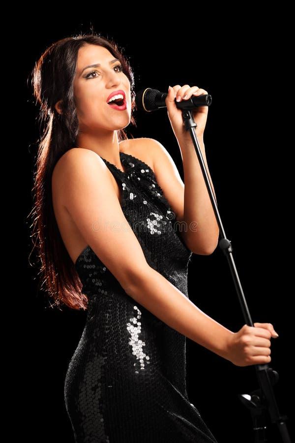 Schöne Sängerin, die auf einem Mikrofon singt lizenzfreie stockfotografie