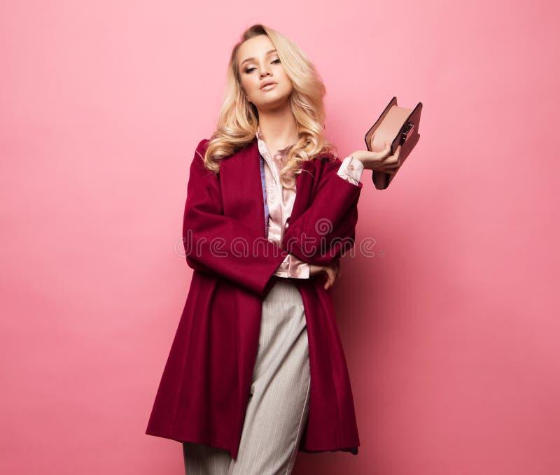 Schöne süße junge Frau, die in der netten Kleidung, roter Mantel, Handtasche aufwirft Frühlingsmodekonzept stockfoto