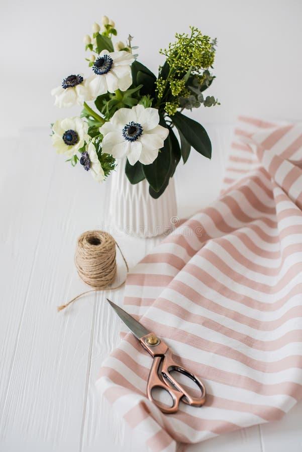 Schöne Scheren, Blumenstrauß von Anemonen, gestreiftes Gewebe stockfotos