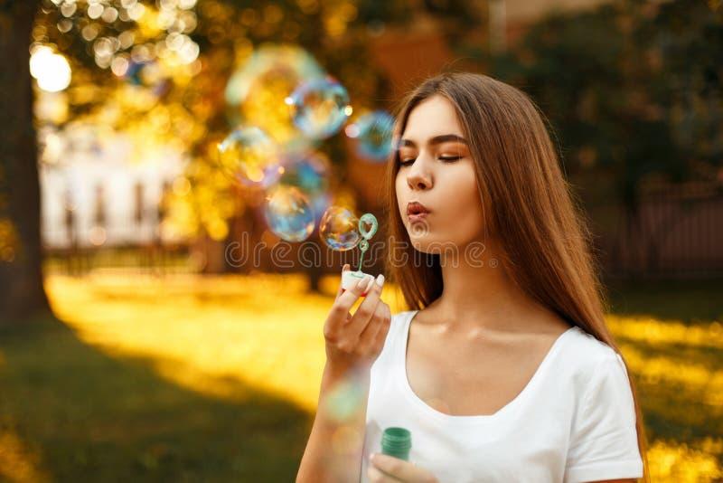 Schöne Schlagseifenblasen der jungen Frau im Park stockbilder