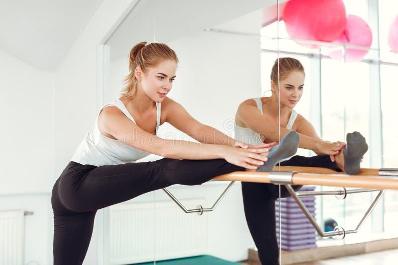 Schöne schlanke Frau in der Sportkleidung, die nahe dem Ballett Barre ausdehnt stockbilder