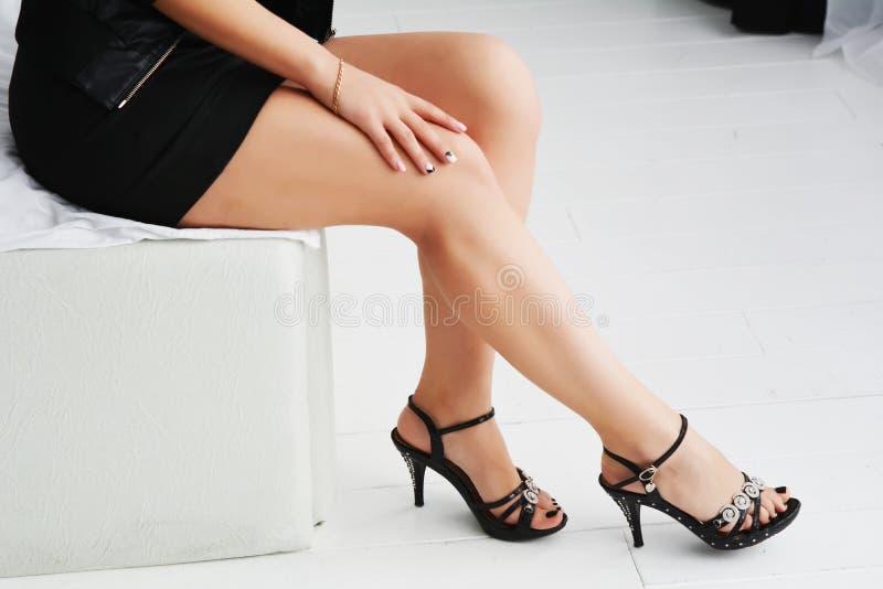 Schöne schlanke weibliche Beine in den Fersen auf einem weißen Hintergrund lizenzfreie stockfotos