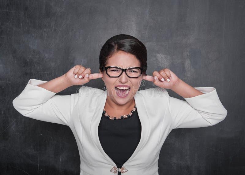 Schöne schreiende Frau mit den Fingern in ihren Ohren auf der Tafel lizenzfreie stockbilder