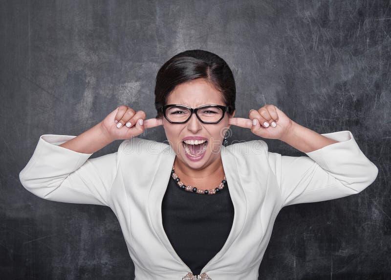 Schöne schreiende Frau mit den Fingern in ihren Ohren auf der Tafel stockbilder