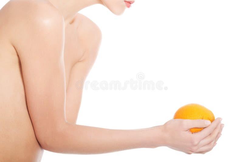 Schöne schulterfreie Frau, die eine Orange hält. lizenzfreies stockbild