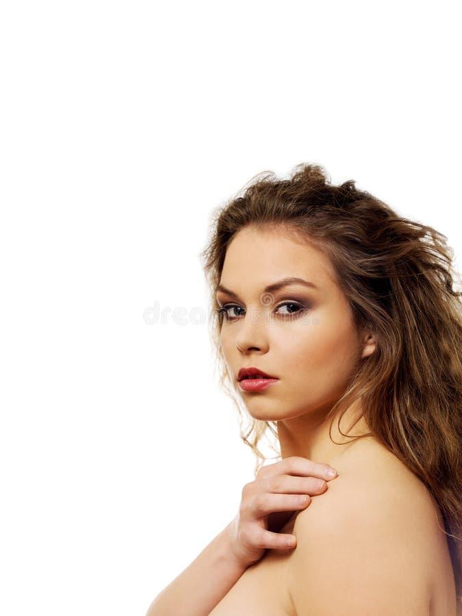Schöne schulterfreie Frau mit dem langen gelockten Haar stockfotos