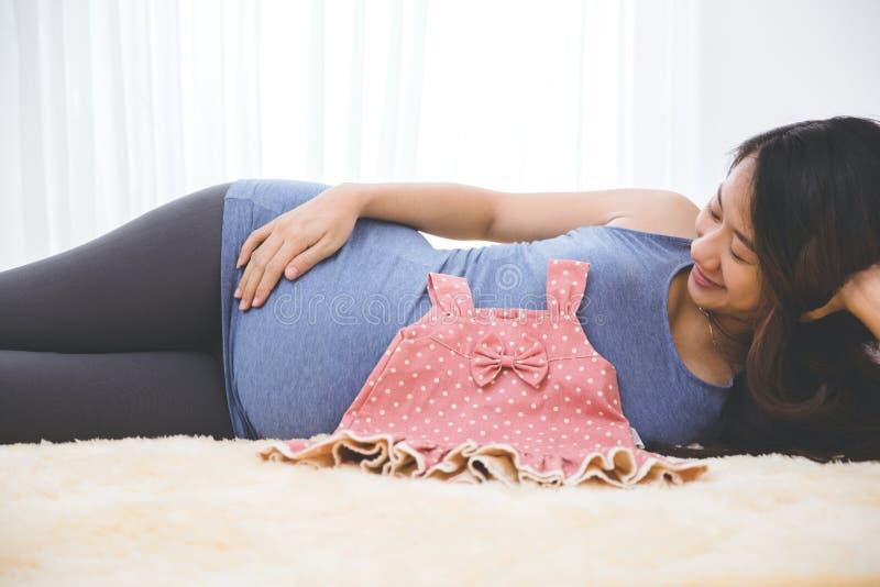 Schöne schwangere asiatische Frau, die auf das Bett mit einem Baby gir legt stockfotos