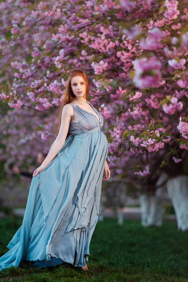 Schöne schwangere Frau in blühendem Garten stockfotografie