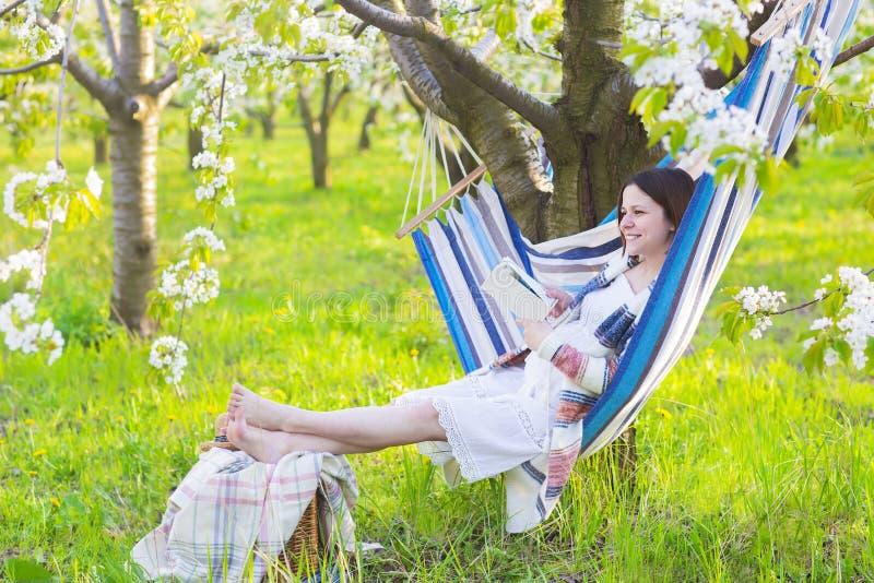 Schöne schwangere Frau in der Hängematte in blühendem Garten lizenzfreie stockbilder