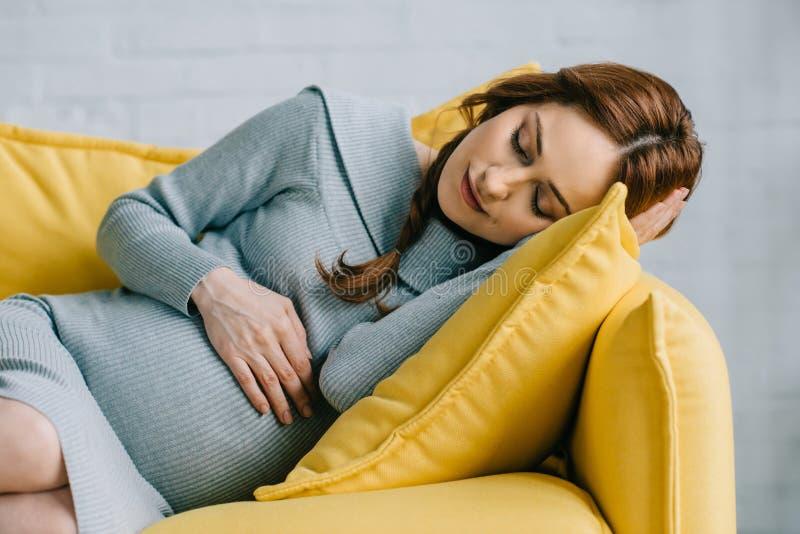 schöne schwangere Frau, die auf gelbem Sofa schläft lizenzfreies stockbild