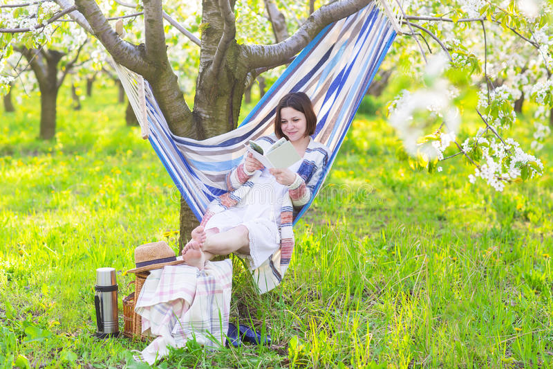 Schöne schwangere Frau, die in der Hängematte in blühendem Garten sitzt lizenzfreie stockfotografie