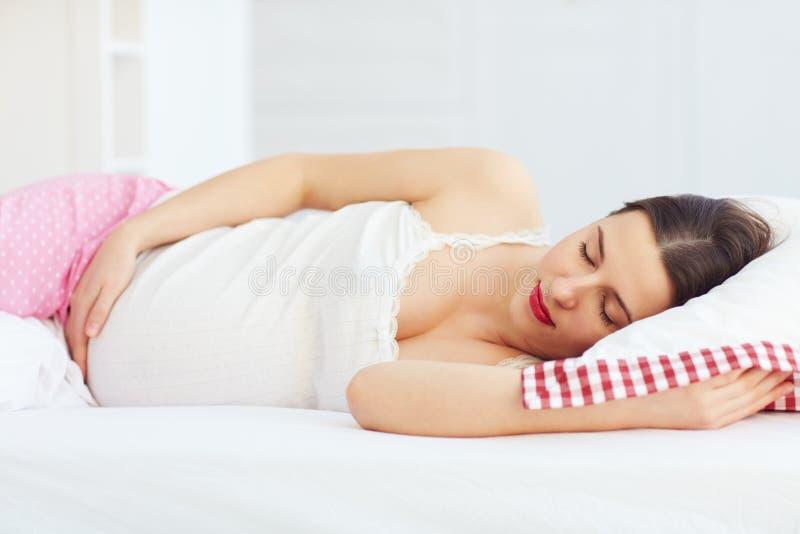 Schöne schwangere Frau, die friedlich im Bett schläft lizenzfreie stockfotografie