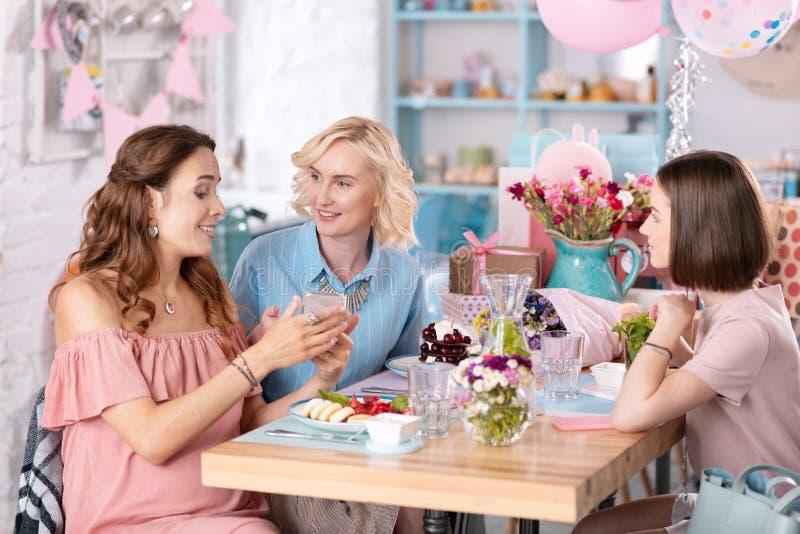 Schöne schwangere Frau, die ihre Freunde haben Babyparty trifft stockbild