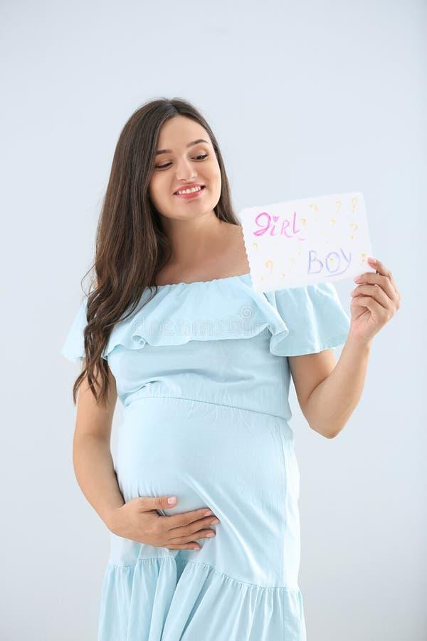 Schöne schwangere Frau, die Papier mit Text JUNGEN hält? MÄDCHEN? auf hellem Hintergrund lizenzfreie stockfotos