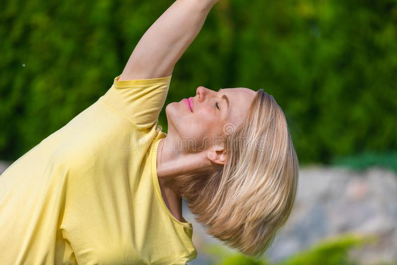 Schöne schwangere Frau, die pränatales Yoga auf Natur tut lizenzfreie stockfotografie