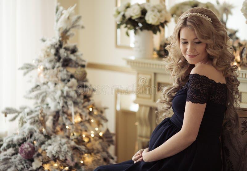 Schöne schwangere Frau in einem Feiertags-Kleid lizenzfreies stockbild