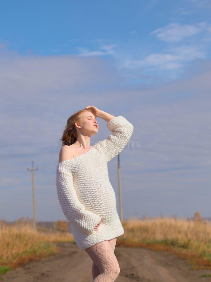 Schöne schwangere Frau in einer weißen woolen Strickjacke auf einer Landstraße stockbilder