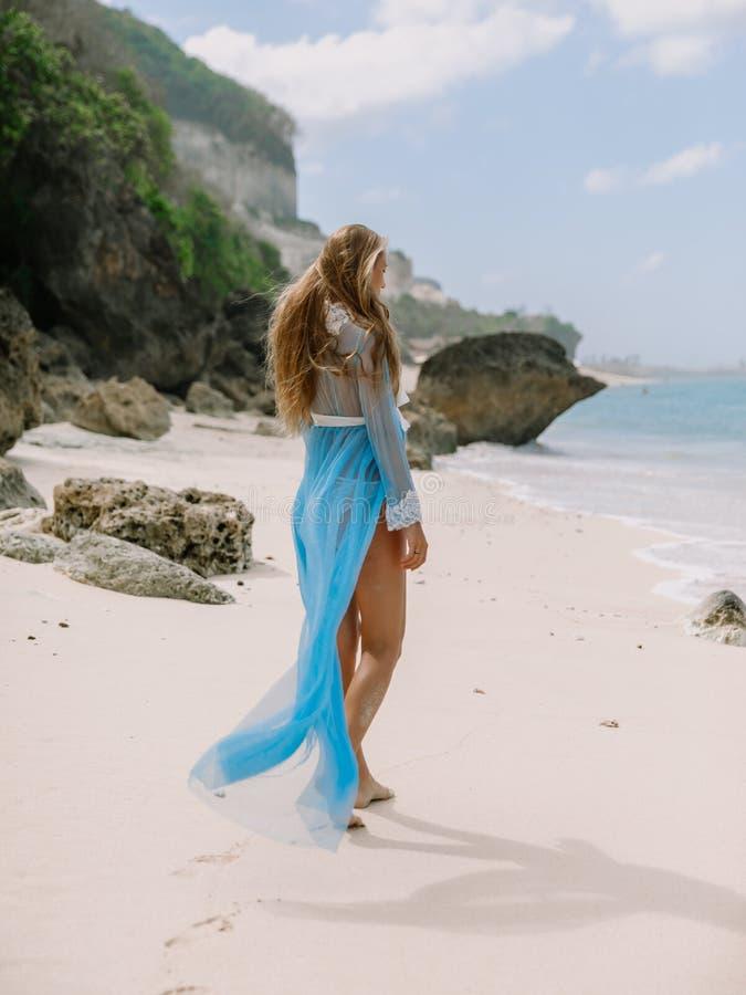 Schöne schwangere Frau im Boudoirkleid Baby am Strand erwartend stockfotos
